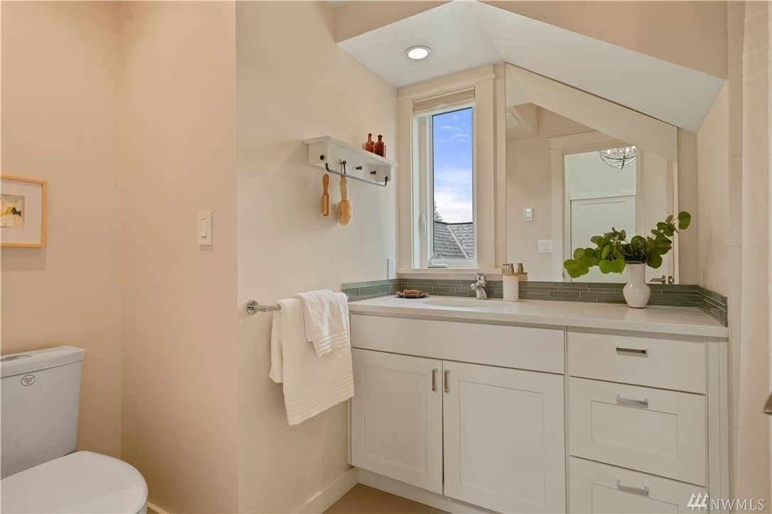 The vanity area of this Craftsman-Style bathroom is built into an alcove with an irregular shed ceiling with a pin light. The wall-mounted mirror follows this irregular shape and extends from the greenish backsplash to the small window above the faucet. The white toilet matches with the beige walls and white cabinets and drawers.
