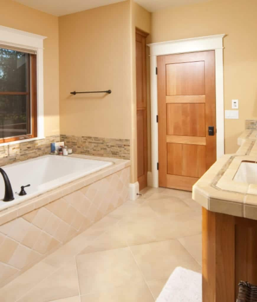 The white wooden finish of the doorway perfectly matches the wooden finish of the window above the bathtub. The beige walls pairs well with the beige tiles of the floor that extend to the side of the bathtub housing. The vanity area has the same tiles for its countertop.