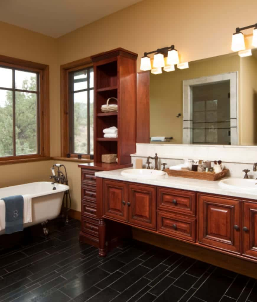 The elegant redwood hues of the built-in cabinets and drawers stand out against the white ceiling and beige walls of this Craftsman-Style bathroom. The redwood hues are contrasted by the white countertops of the vanity area and the white freestanding bathtub. These are complemented by the dark tiles of the floor.