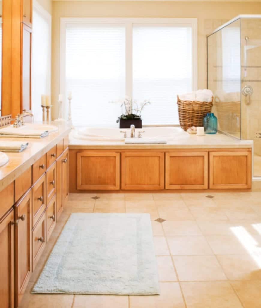 This bathroom has wooden tones and beige hues that remind you of the warmth and relaxation of being at home with your family. The bathtub is fitted into a marble housing with a wooden finish that mirrors the drawers and cabinets.