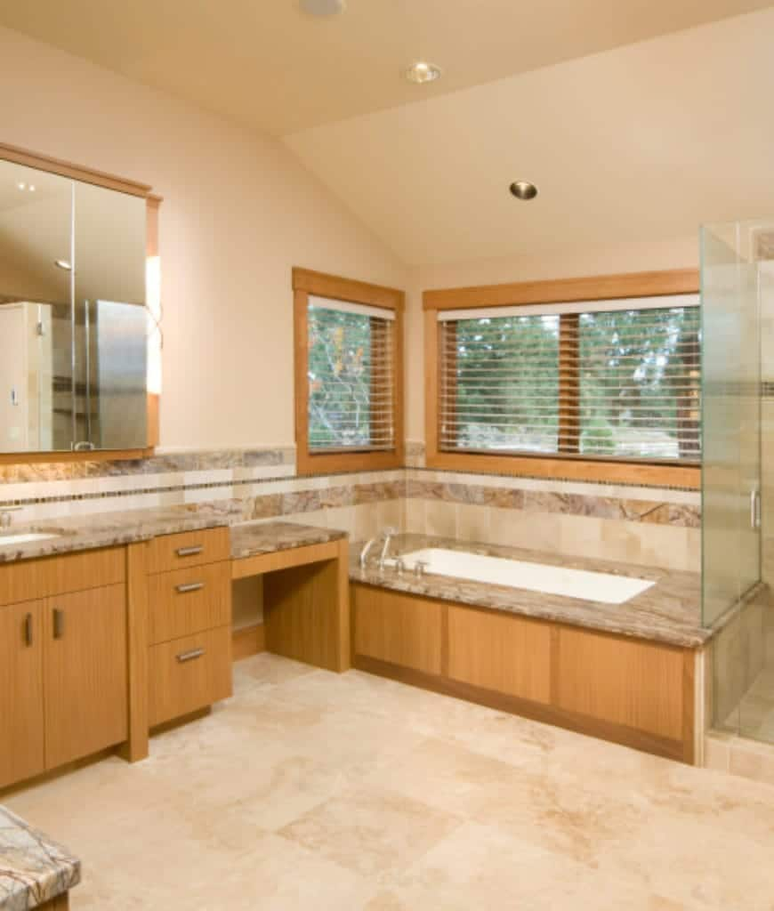 The irregular beige vaulted ceiling pairs well with the beige walls and beige marble flooring. This monotone provides a nice background for the wooden tones of the cabinets and drawers that extend to the wooden housing of the bathtub.