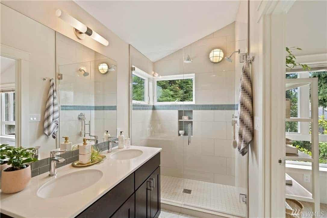 This bathroom has a vanity area with two faucets and sinks topped with a wide wall-mounted mirror that is illuminated by the warm yellow light of a modern lamp above it. The built-in cabinet has a dark wood finish that stands out against the white tiles of the shower area.