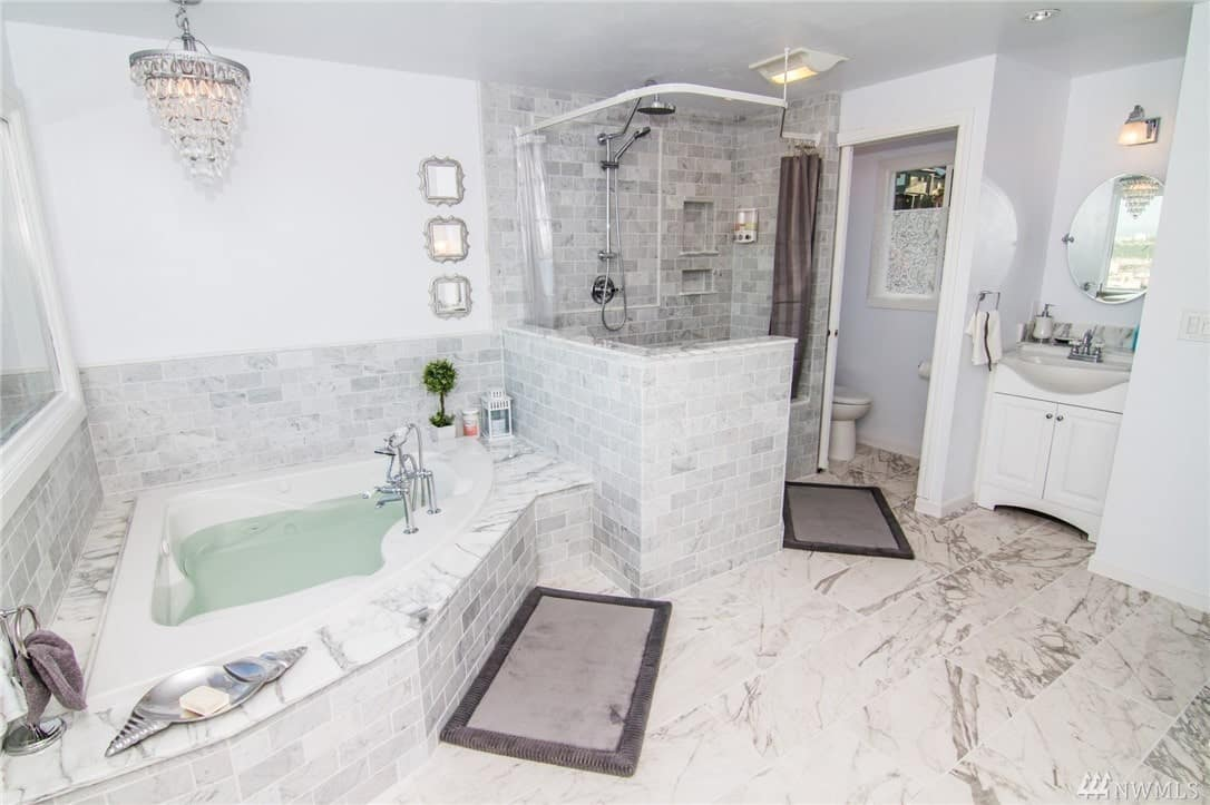 This Craftsman-Style bathroom has white marble flooring that extends to the housing of the bathtub. The walls are fitted with white tiles arranged in a brick wall pattern. There is a lovely crystal chandelier hanging over the bathtub that matches the wall-mounted lamp over the small vanity area.