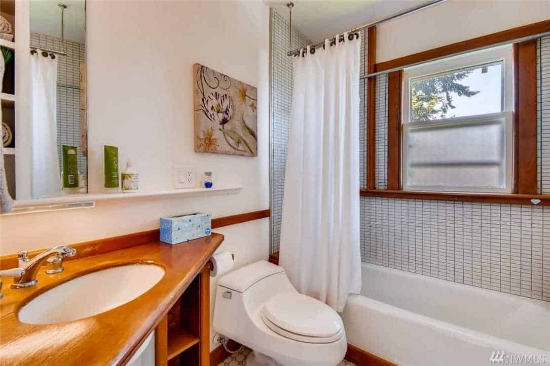 The charming corner vanity area has a wooden countertop that holds the white sink and dual-knob faucet. The wooden element matches the accents of the white walls and the frames of the bathtub and the window above it. A lovely wall-mounted floral artwork gives color to the white walls.