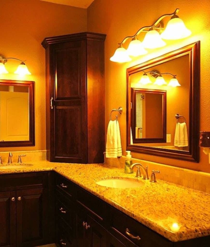This Craftsman-Style bathroom is radiating with the warm yellow light coming from the wall-mounted lamps positioned above the two elegant mirrors of the L-shaped peninsula of the two vanity areas with dark wooden cabinets and drawers.