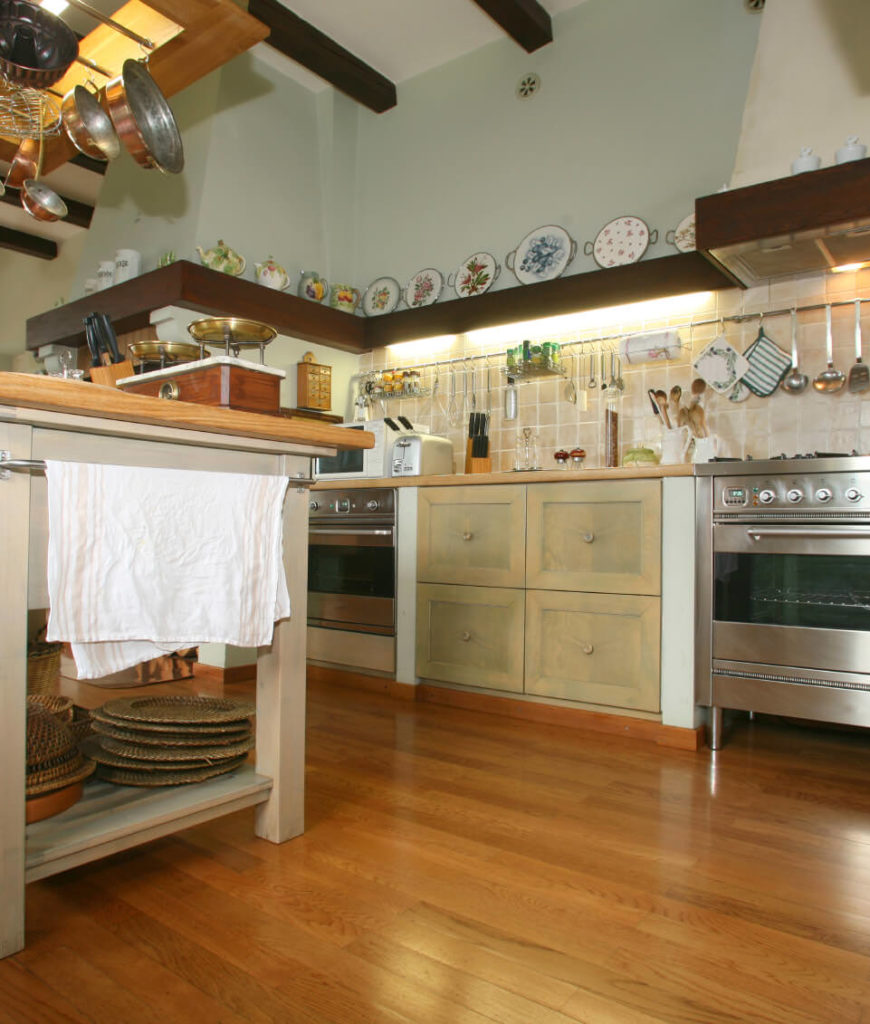 Farmhouse kitchen with beam ceiling, pot rack, built-in shelving displaying ceramics and a kitchen island table.
