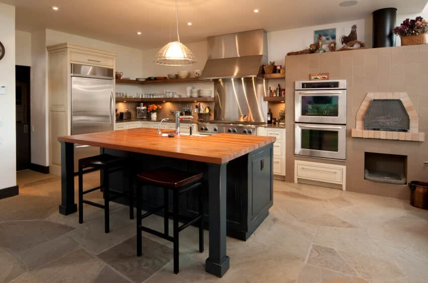 A kitchen featuring a wood-top stylish center island breakfast bar lighted by a pendant and recessed lights.