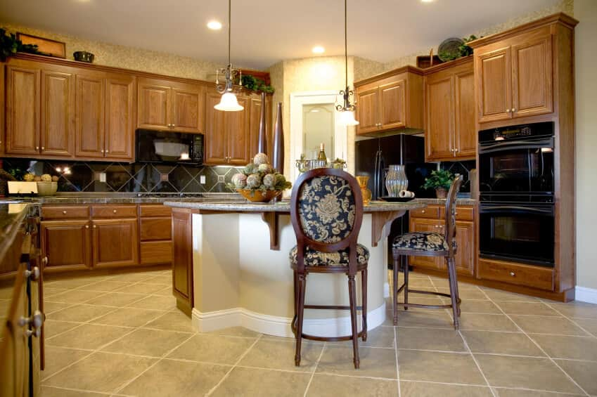 Brown U-shaped kitchen with pendant lights, black appliances, central island and tile flooring.