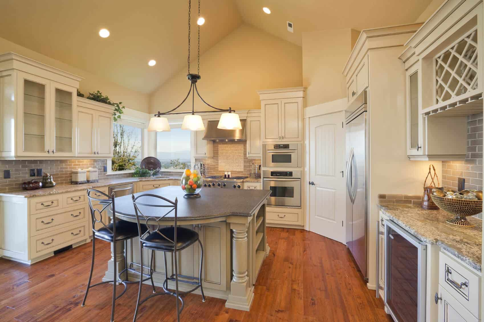 Large U-shaped kitchen with tall ceiling, chandelier, picture windows and hardwood flooring.