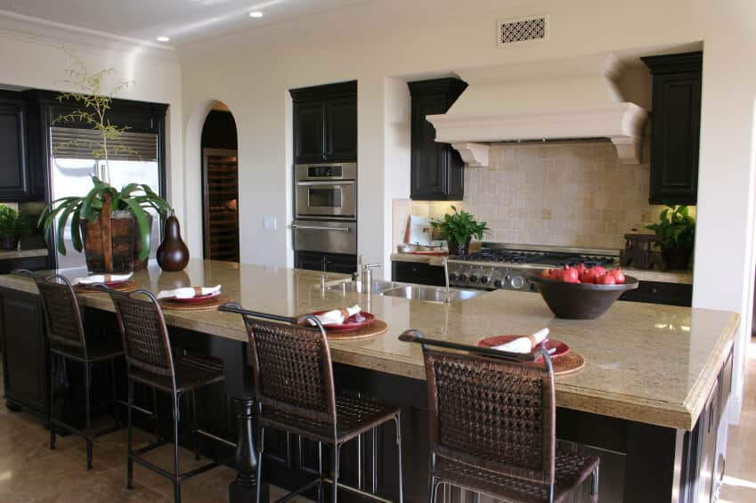 Wicker counter chairs sit at a breakfast island fitted with dual sink and chrome fixtures in this tropical kitchen. It has black cabinetry and beige range hood fixed on the marble tiled backsplash.
