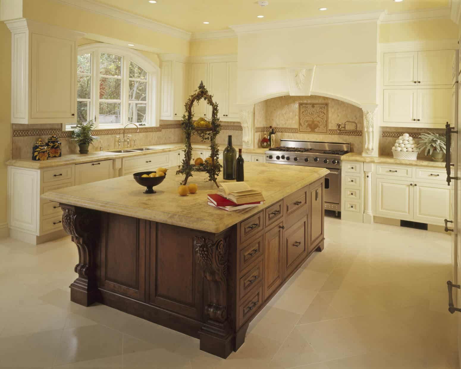 Traditional kitchen with white cabinets, yellow walls, large center island and tile flooring.