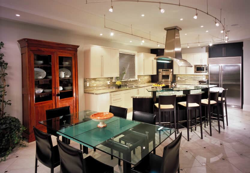 Modern eat-in kitchen with a curved island bar topped with a raised glass counter that's aligned with black bar stools. It is lighted by track lights surrounding a stainless steel vent hood.