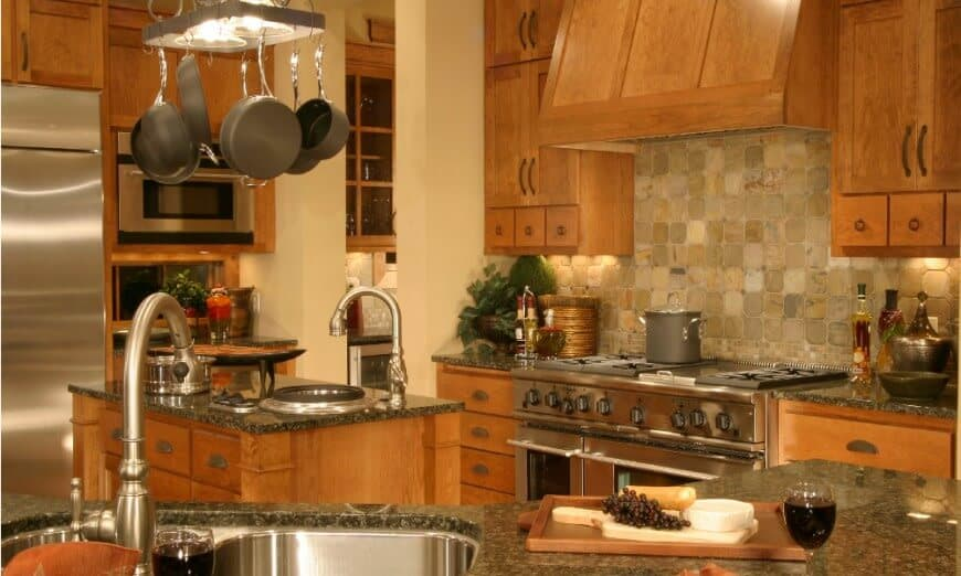 Brown kitchen with pot rack, medium-tone wood cabinet, a central island with a sink and stone tile backsplash.