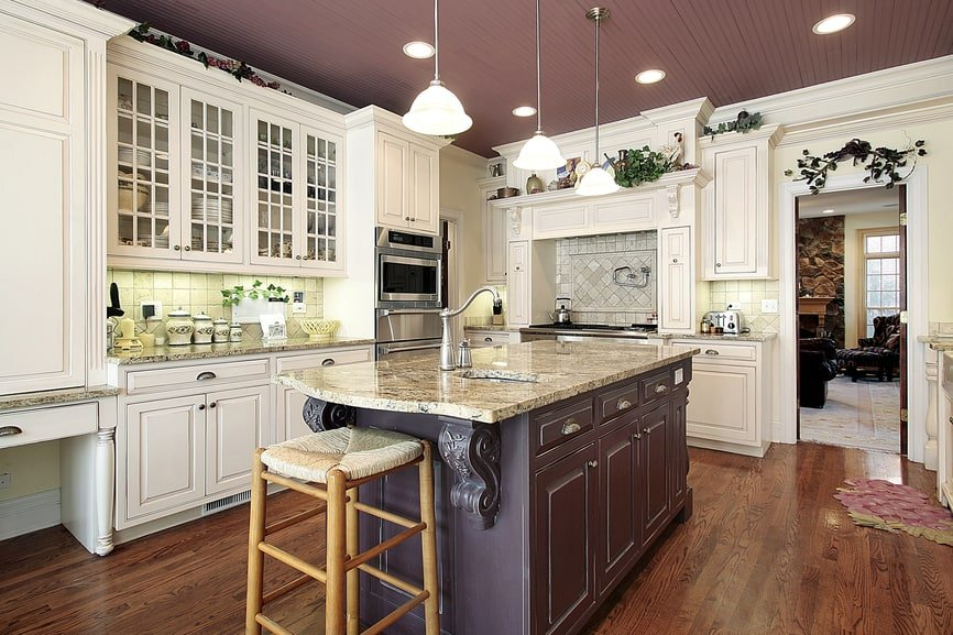 White L-shaped kitchen room with farmhouse style cabinetry, brown kitchen island, pendant and recessed lights.