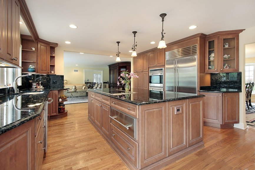 Roomy brown palette kitchen with hardwood floors, large kitchen island, marble countertops, recessed lights, and a row of decorative pendant lights.