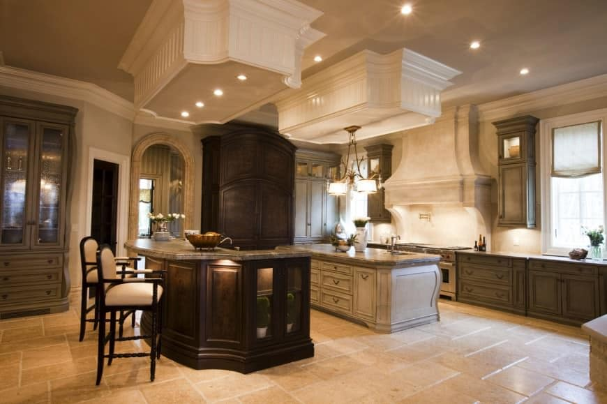 Large shabby-chic kitchen with chandelier, an arched doorway and 2 islands, one with a breakfast bar lighted by recessed lights.