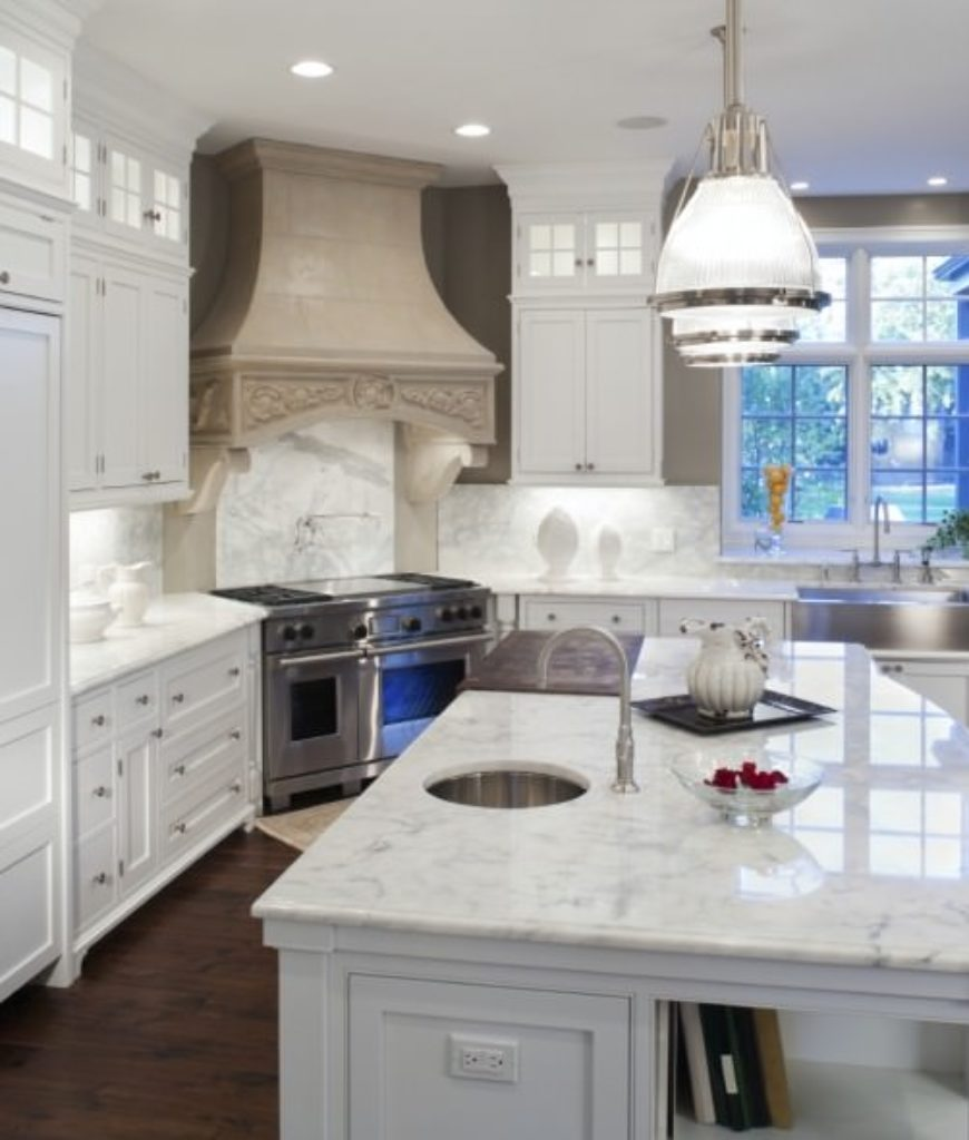 White kitchen with recessed panel cabinetry, pendant lights, central island and hardwood flooring.