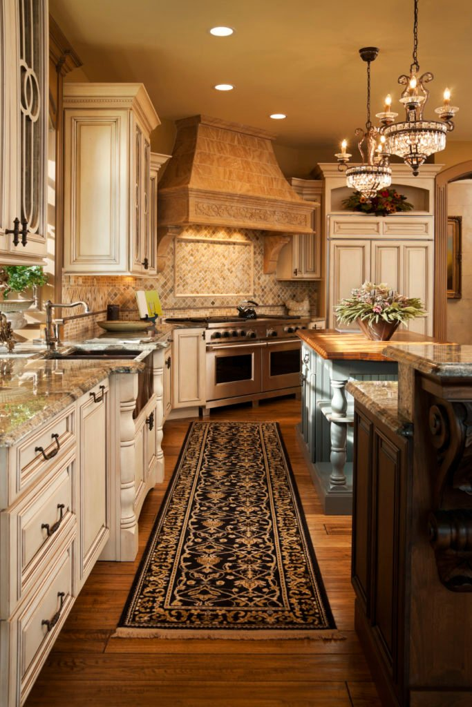 Warm elegant residential kitchen designed with high end finishes including hard wood floors, granite counter tops, custom cabinets, two islands, elegant chandeliers, large stove hood, and two stainless steel ovens.