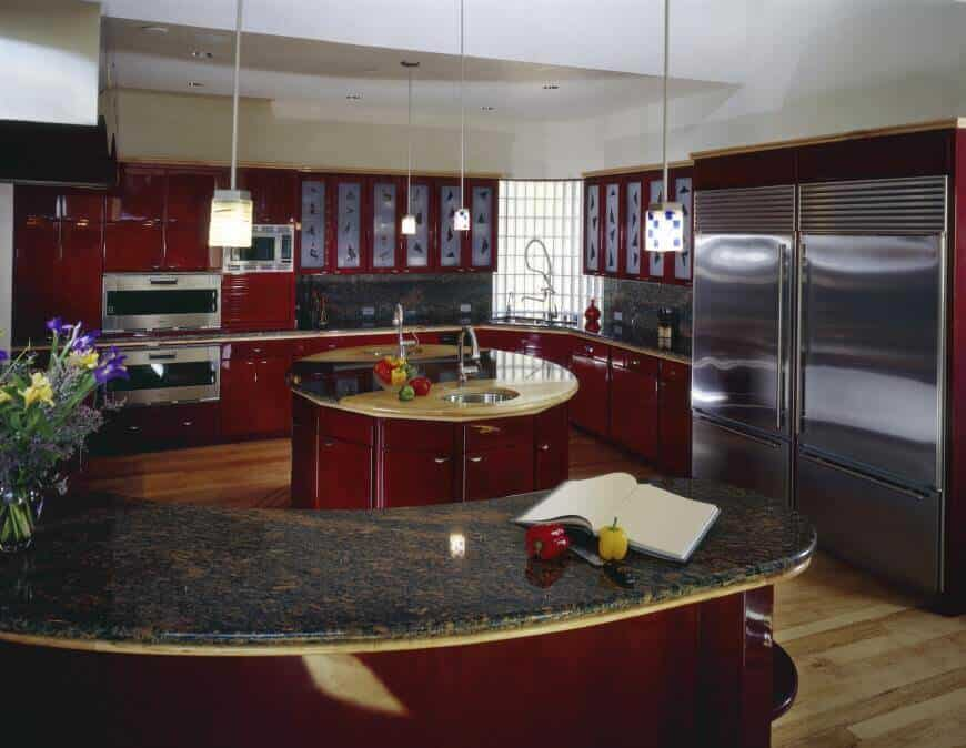 Red modern kitchen in g-shape with pendant lighting, stainless steel appliances, a central island and peninsula.