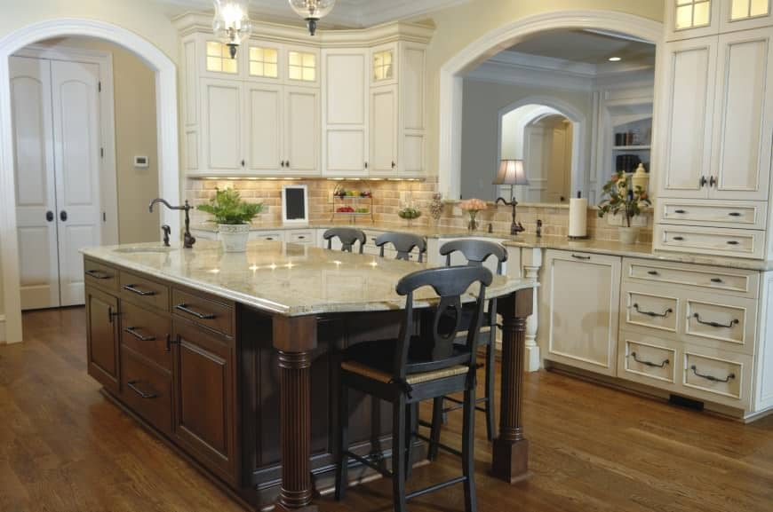 Farmhouse kitchen with arched doorway and window in between white cabinetry and above brick tile backsplash. It includes a dark wood breakfast island topped with a white marble counter and fitted with a round sink.