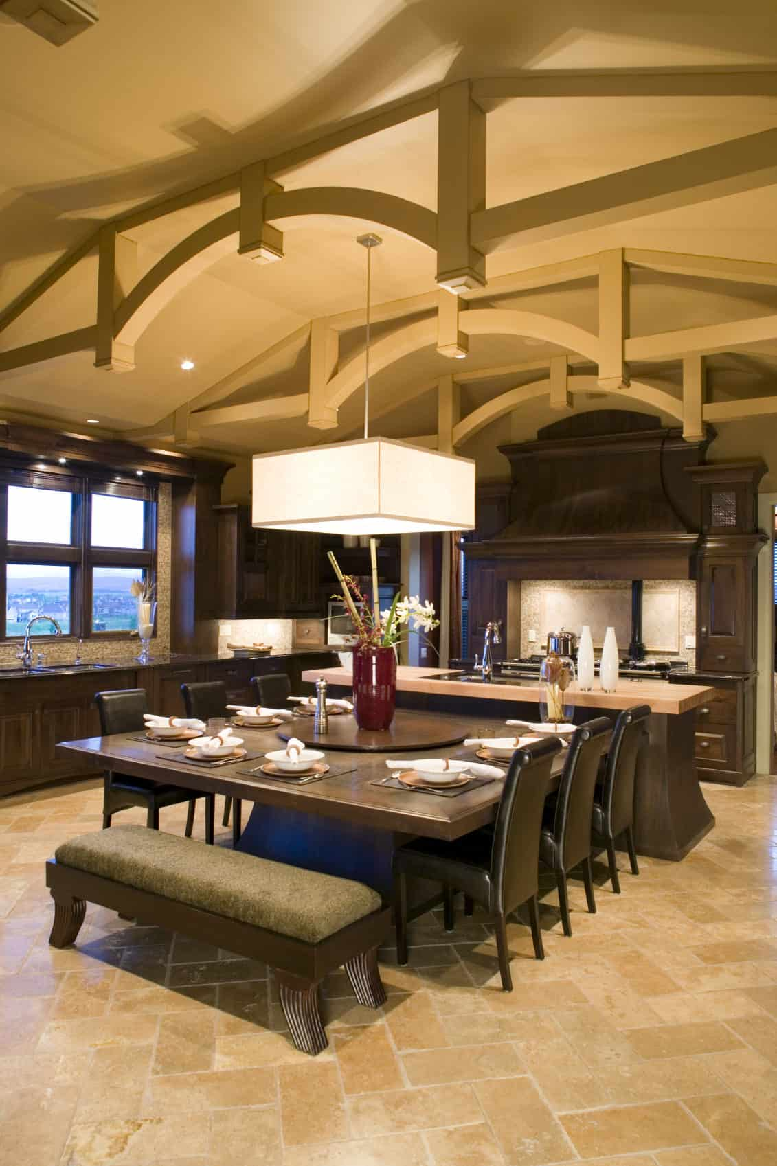 Massive dine-in-kitchen with beam ceiling, large pendant lighting and tile flooring.
