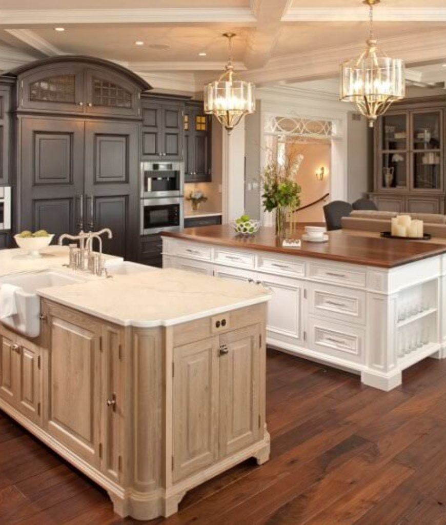 Single wall great room kitchen with coffered ceiling, chandelier, farmhouse sink and 2 islands.