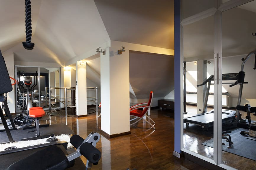 Luxurious home gym with treadmill and free weights with mirrors on the wall and wood floors.
