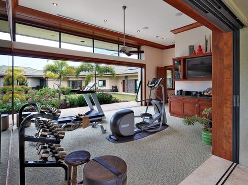 A large, tropical-style home gym with carpeted floors and recessed lights.