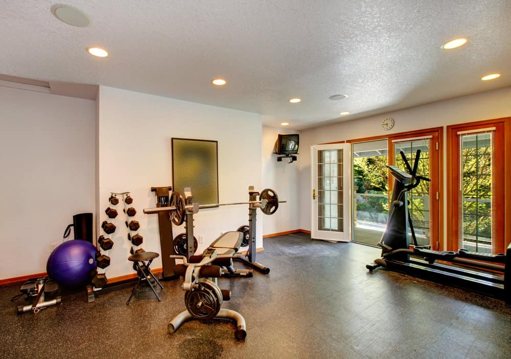 A spacious home gym with recessed lights in a contemporary style.