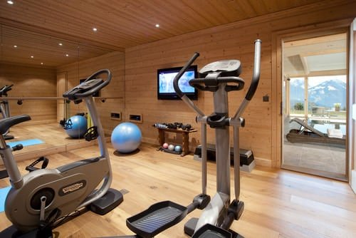 A contemporary home gym with hardwood floors and walls.