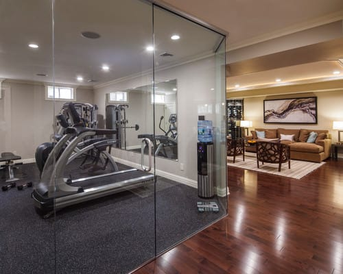 A home gym with glass walls and carpeted floor.