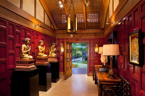 Large Asian foyer with matching wood wall panels and front door and dramatic lighting on the Buddhist sculptural displays.