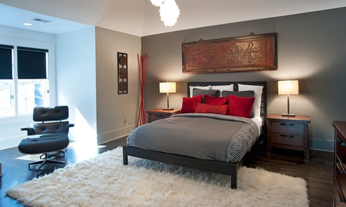 Mid-sized Asian master bedroom with dark hardwood flooring and gray walls featuring a wooden Japanese calligraphy.