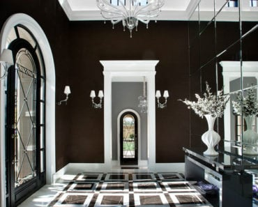 Contemporary foyer with tall ceiling, a chandelier, black walls and a full wall mirror.