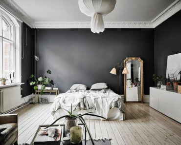 Large Scandinavian master bedroom with cove ceiling, black walls and light wood flooring.