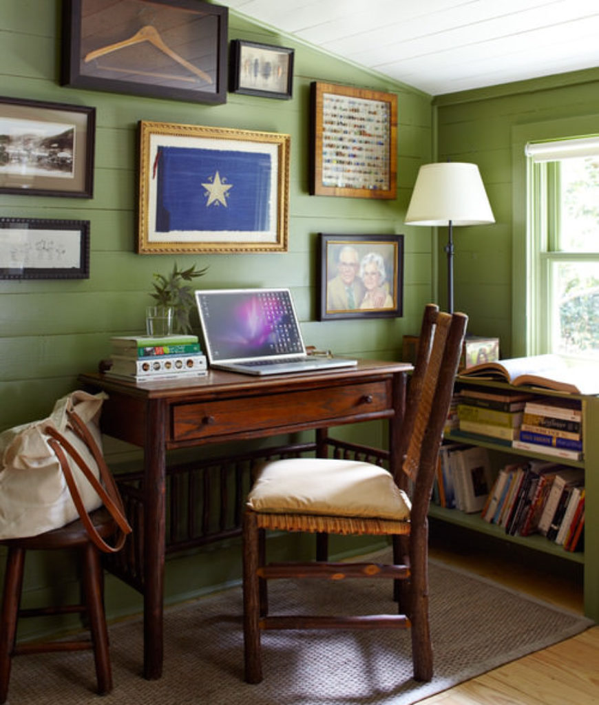 Tiny Farmhouse home office with beam ceiling, some antique furniture pieces and green shiplap panel walls featuring frames of family memories.