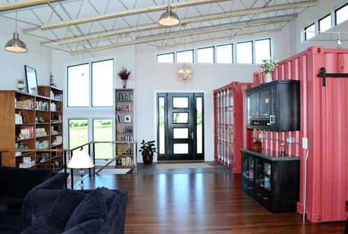 Industrial foyer with exposed ductwork, pendant lighting, white walls, freestanding shelves and dark front door.
