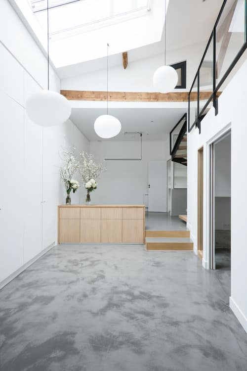 Large Industrial white foyer with shed ceiling, skylights, pendant lighting and concrete flooring.