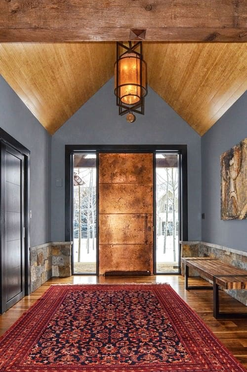 Industrial Foyer With Bamboo Beam Ceiling Gray Walls Copper Front Door Stone Wainscoting Design And Hardwood Flooring A Large Rustic Rug