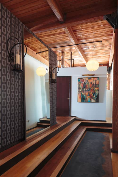 Industrial foyer with dark rust beam ceiling, pendant lighting, white walls and medium tone hardwood flooring.