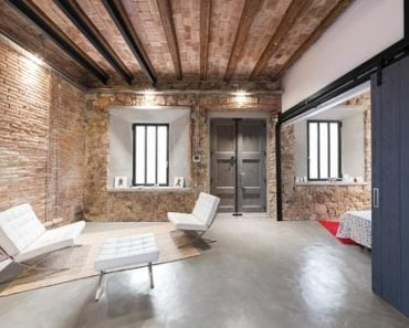 Mid-sized Industrial foyer with beam ceiling, exposed brick wall and a cozy seating area on concrete flooring.