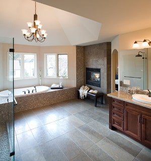 Master bathroom with fireplace, chandelier, and tiled floors.