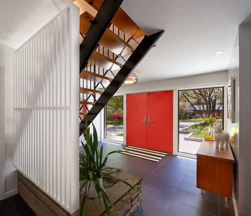 Midcentury foyer with red double front doors, a console table and slate tile flooring.