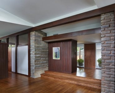 Midcentury foyer with a combination of wooden and stone elements emphasizing a clean aesthetic.