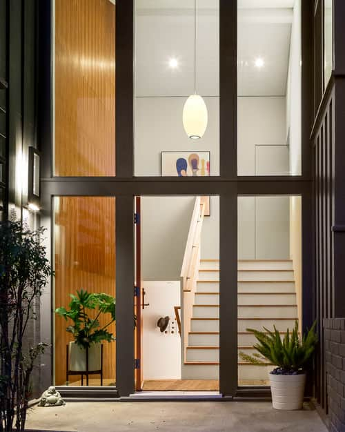 Midcentury foyer with 2-story ceiling and glazed walls where the straight staircase can be easily seen from the outside.