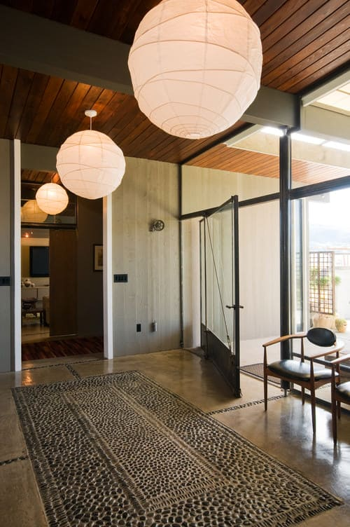 Elegant large Midcentury foyer with beam ceiling, paper lantern pendant lighting and glazed walls and front door.