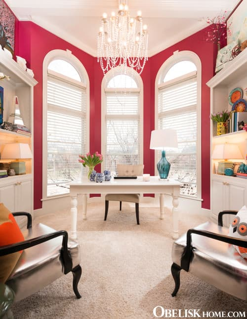 Large Eclectic Home Office With Pink Walls, Chandelier And Carpet Flooring.