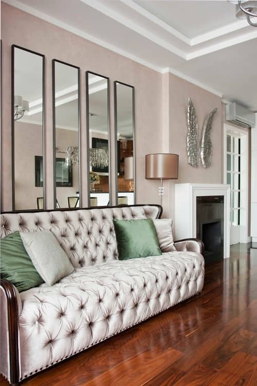 large victorian living room with pink walls hardwood flooring and a tufted sofa beside the - Decorating Ideas For Living Rooms With Fireplaces