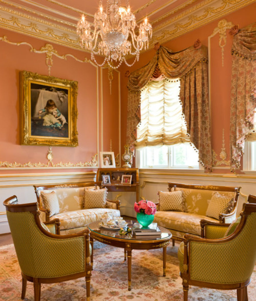 Large Victorian formal living room with gilded crown molding, pink walls, chandelier and French chairs.