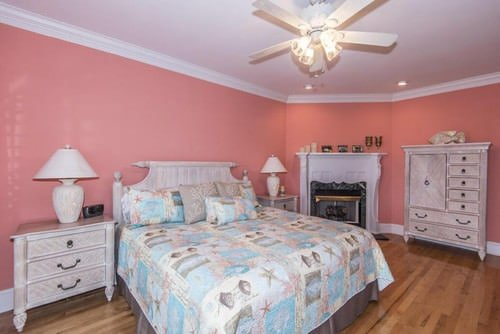 Beach Style Master Bedroom With Ceiling Fan Light Pink Walls And A Corner Fireplace